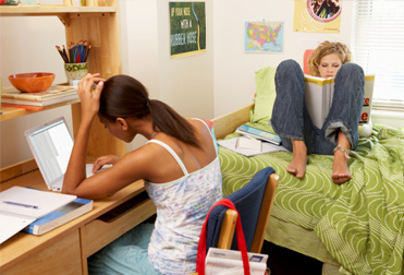 Two young women studying in dorm room