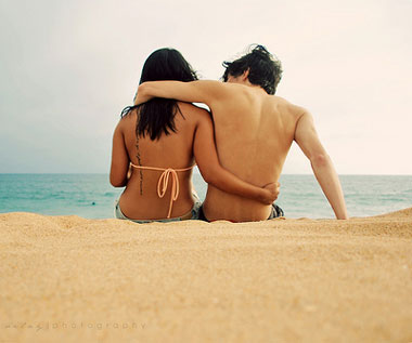 Couple sitting on the beach with arms around each other